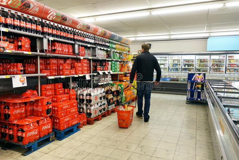 Interior of a Delhaize supermarket. KAPELLEN, BELGIUM - MARCH 2019: Aisle containing exclusive Coca-Cola Company products in a Delhaize supermarket royalty free stock image