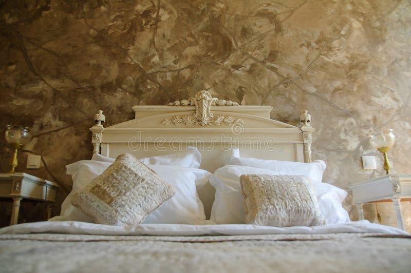 Interior design alla moda della camera da letto dell'oro con i cuscini su letto matrimoniale in hotel fotografie stock libere da diritti