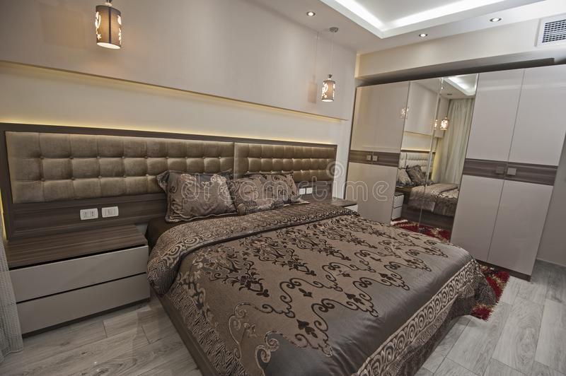 Interior design of bedroom in house. Interior design decor furnishing of luxury show home bedroom with furniture and double bed royalty free stock photos