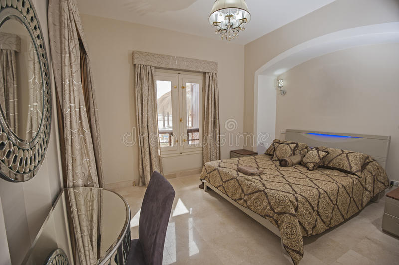 Interior design of bedroom in house. Interior design decor furnishing of luxury show home bedroom with furniture and mirror stock photo