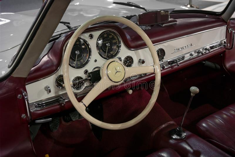 Interior design of a classic and vintage Mercedes Benz in maroon and white stock images