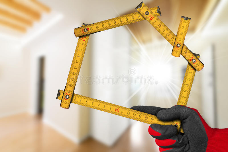 Interior Design Concept - Wooden Ruler. Interior Design Concept - Hand with work glove holding a wooden meter ruler in the shape of house. Interior of a blurred royalty free stock photography