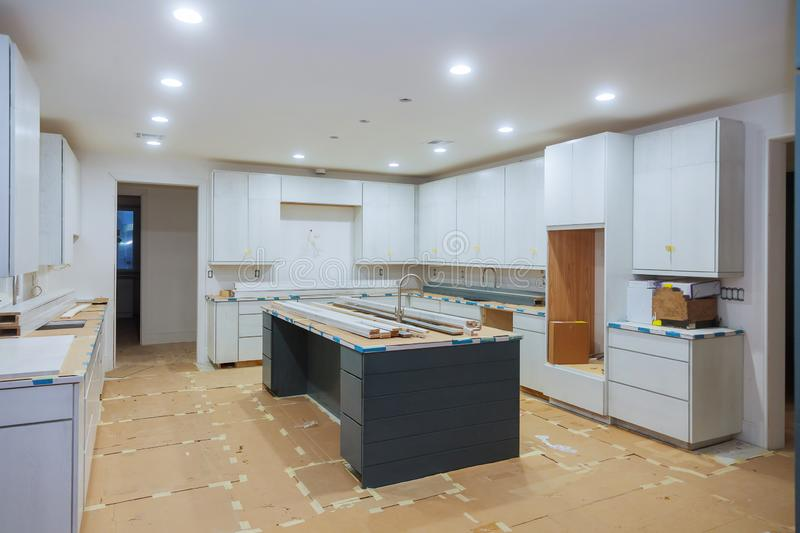 Interior design construction of a kitchen with cabinet maker installing custom. Interior design construction of kitchen with cabinet maker installing custom stock photo