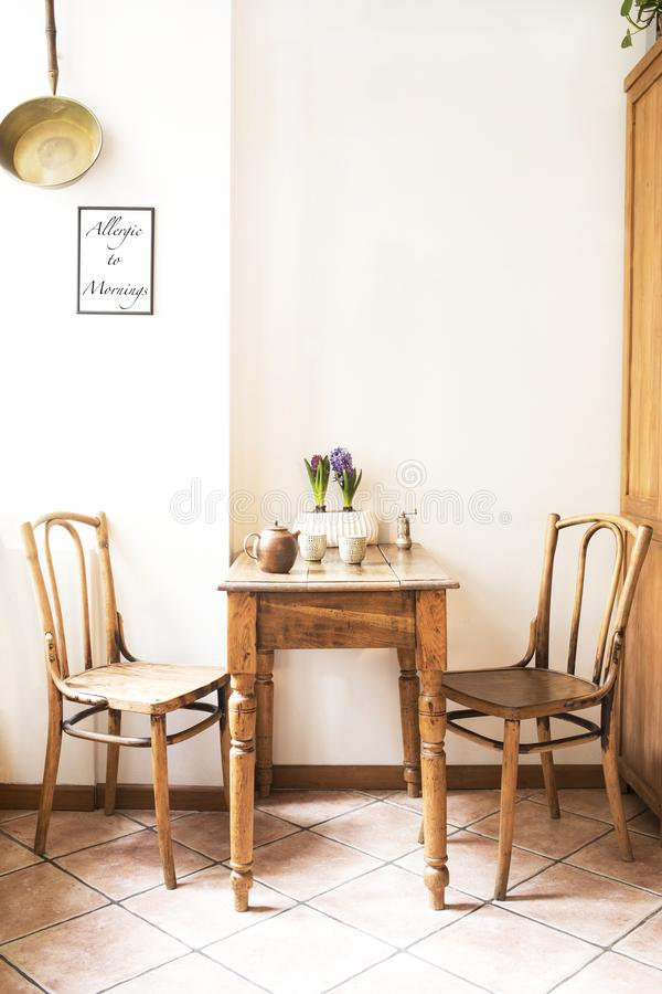 Interior design d'annata dello spazio della cucina con la piccola tavola contro la parete bianca con le sedie e le decorazioni se fotografia stock libera da diritti