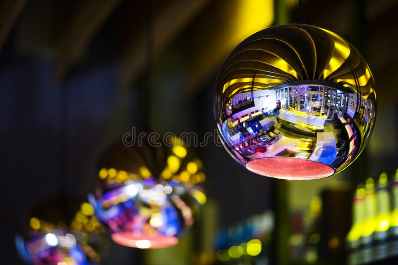 Interior design detail in modern trendy bar at night. Contemporary interior design silver lamp detail in modern trendy bar at night royalty free stock images