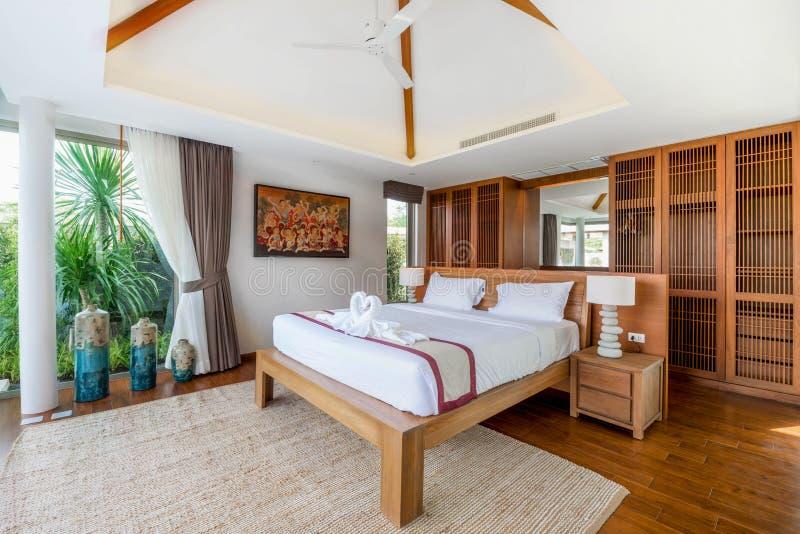 Interior design di lusso in camera da letto della villa dello stagno con il letto accogliente con il soffitto sollevato alto nell fotografia stock
