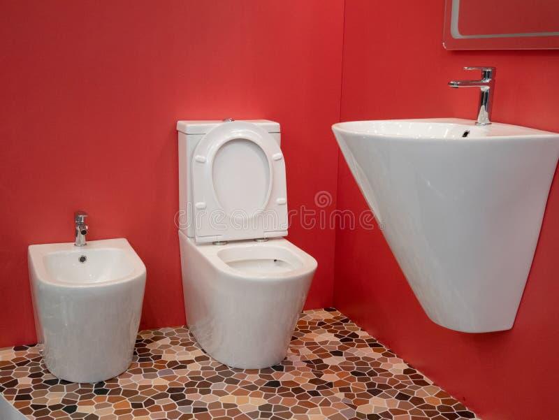 Interior design domestico moderno del bagno con il lavandino bianco, la toilette, il bidet e le pareti rosse vive immagine stock libera da diritti