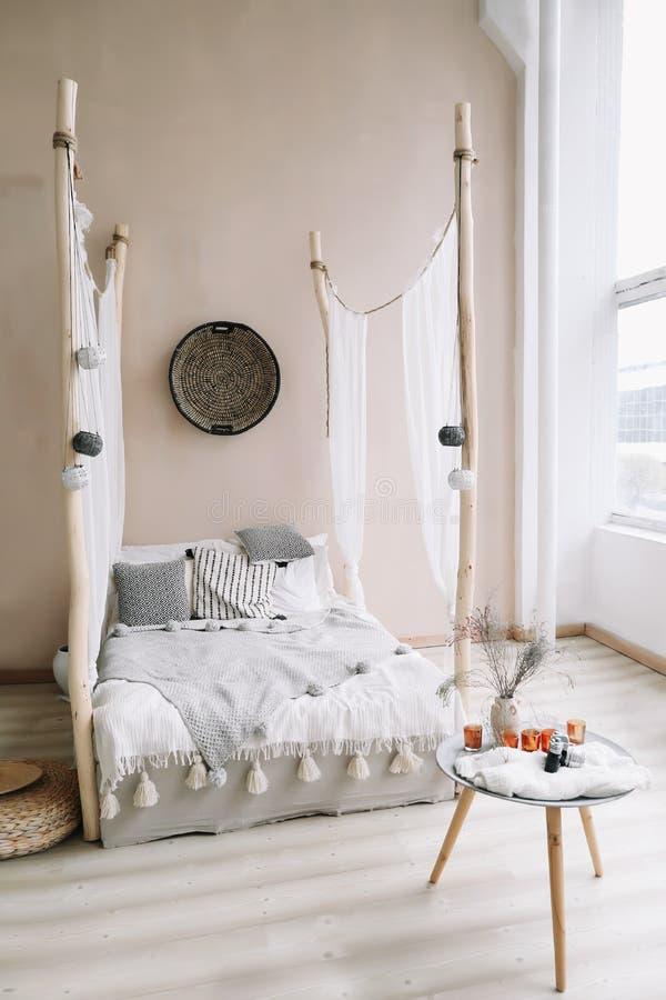 Interior design domestico moderno Letto con i cuscini, coperta Interno esotico della camera da letto, stile scandinavo immagini stock libere da diritti