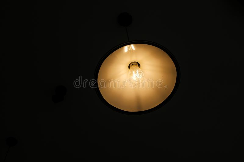 Interior design of lamp. A LED light bulb is illuminating and hanging under a house roof. Lighting lamp under the ceiling. Interior design of Vintage and royalty free stock photo