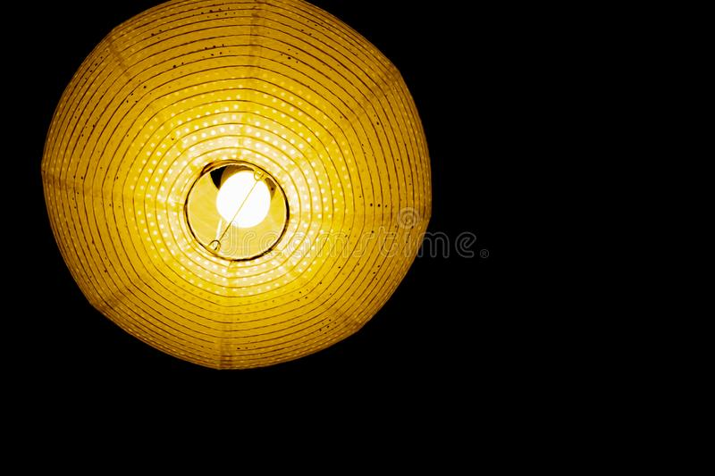 Interior design of lamp. A LED light bulb is illuminating and hanging under a house roof. Lighting lamp under the ceiling. Interior design of Vintage, Paper stock photos
