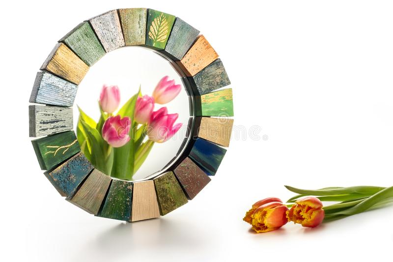 Interior design mirror handmade in wooden frame with bouquet of spring tulips. Interior design mirror handmade in wooden frame with painted cracks aged paints royalty free stock images