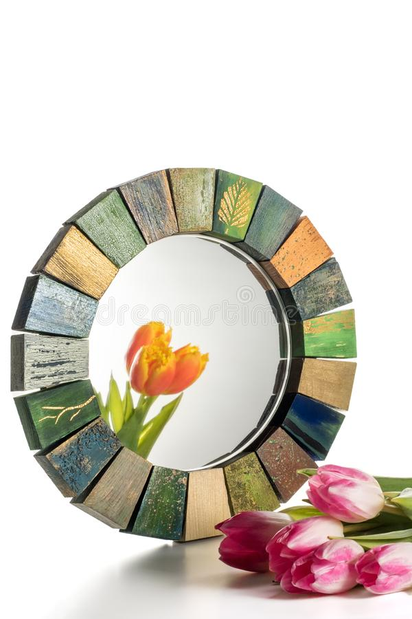 Interior design mirror handmade in wooden frame with bouquet of spring tulips. Interior design mirror handmade in wooden frame with painted cracks aged paints stock images