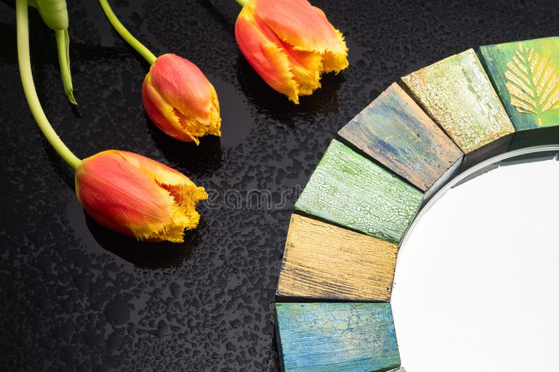 Interior design mirror handmade in wooden frame with bouquet of spring tulips. Interior design mirror handmade in wooden frame with painted cracks aged paints royalty free stock photography