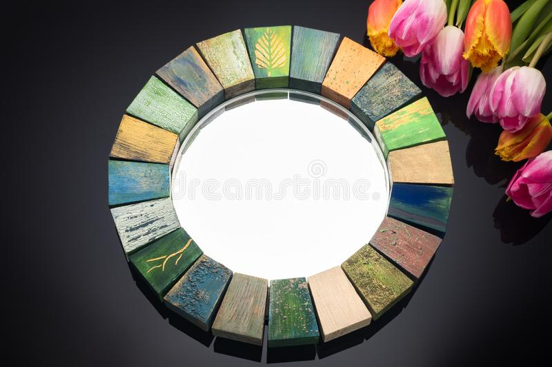 Interior design mirror handmade in wooden frame with bouquet of spring tulips. Interior design mirror handmade in wooden frame with painted cracks aged paints stock photography