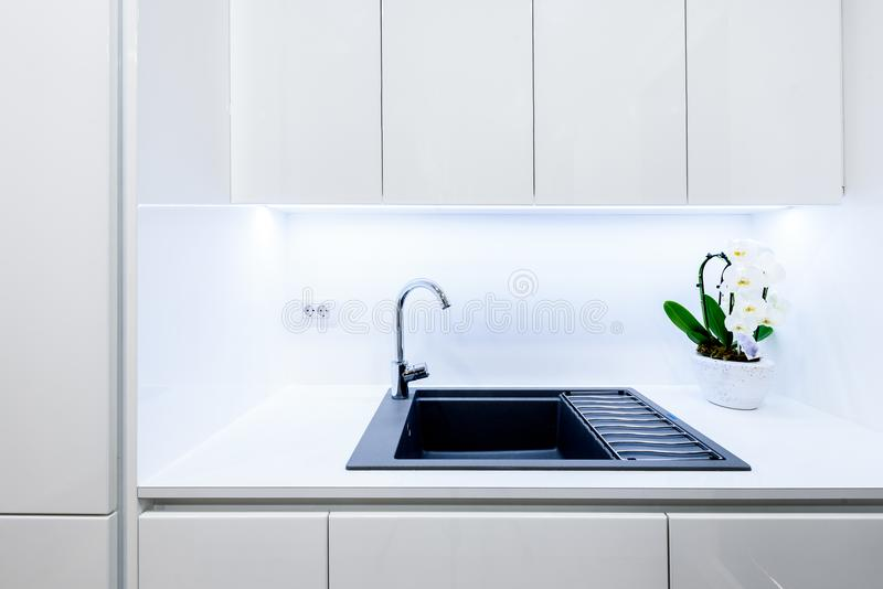 Interior design new modern white kitchen with kitchen appliances. Luxury residential kitchen with sink, stove, hob and white wooden cupboards and hard wood royalty free stock photos