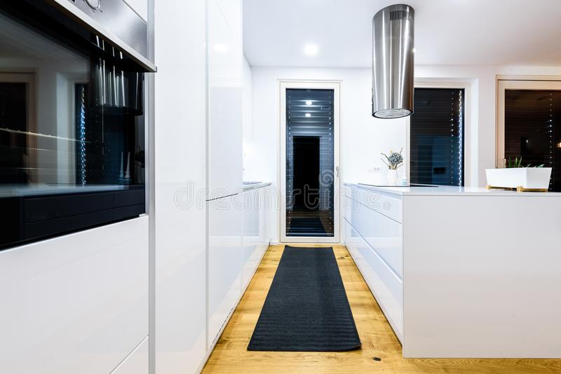 Interior design new modern white kitchen with kitchen appliances. Luxury residential kitchen with sink, stove, hob and white wooden cupboards and hard wood stock photography