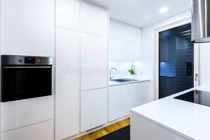 Interior design new modern white kitchen with kitchen appliances. Luxury residential kitchen with sink, stove, hob and white wooden cupboards and hard wood stock photos