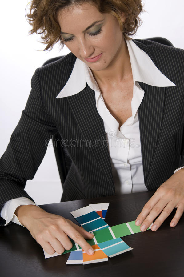 Interior Designer Architect Choosing Swatches. A business woman (possibly an interior decorator,designer or architect) looking through swatches (paint color royalty free stock photography