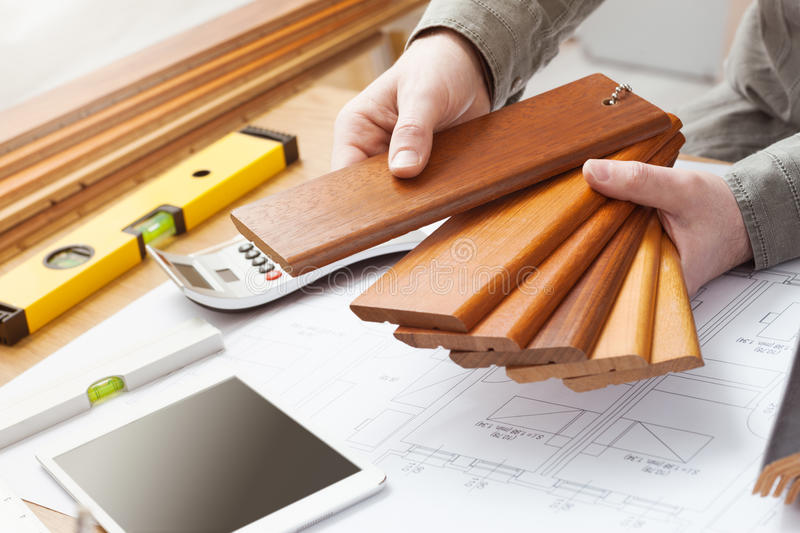 Interior designer choosing a baseboard. Professional interior designer holding wood swatches for baseboard and skirting, hands close up with desktop, house stock photography