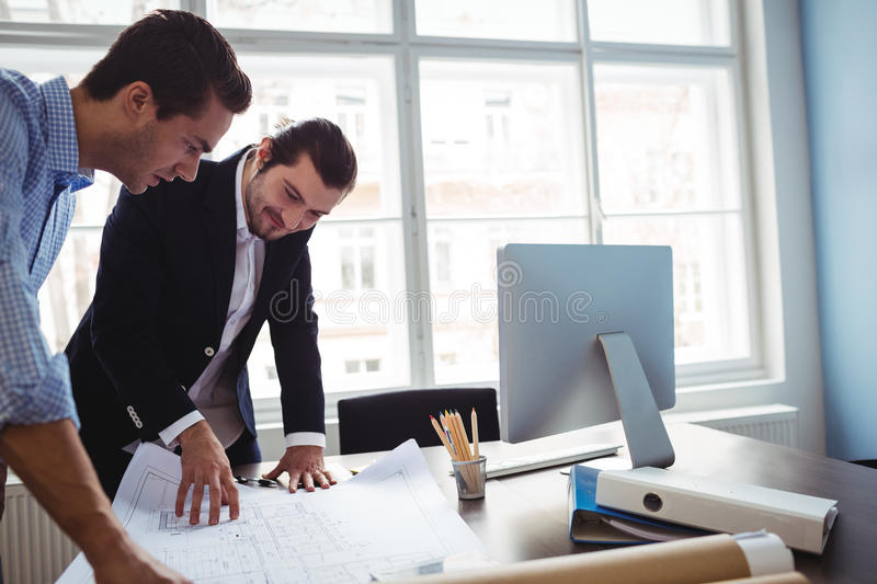 Interior designer discussing blueprint with colleague royalty free stock images