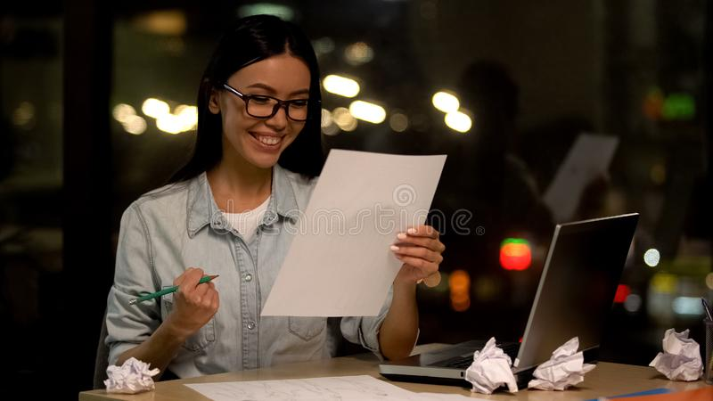 Interior designer looking at sketch showing yes gesture, satisfied with work stock photo