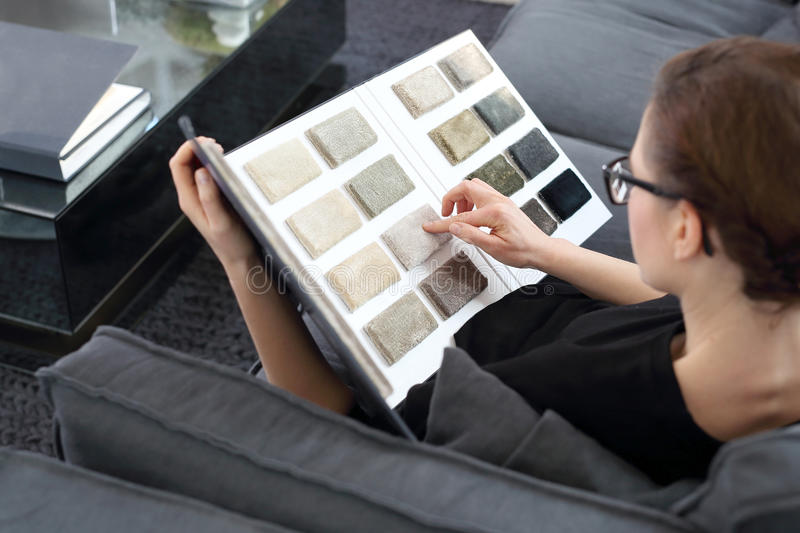 Interior designer with the probe carpets. Woman chooses carpet for the living room stock images