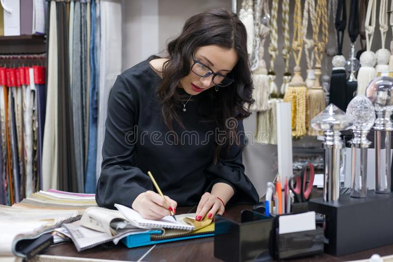 Interior designer, at the workplace in the office. With samples of fabrics and accessories for curtains and upholstery royalty free stock images