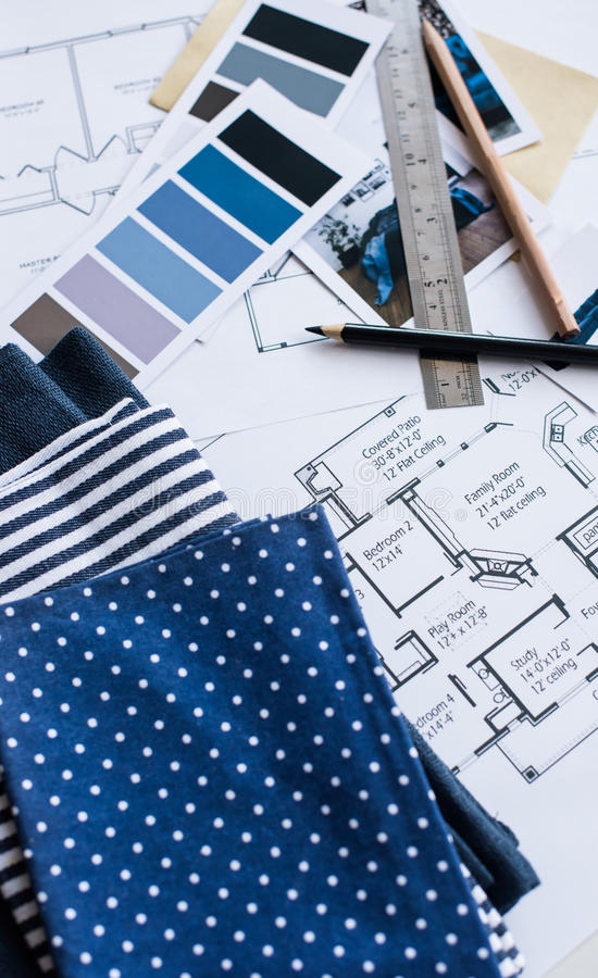 Interior designers working table. Interior designer's working table, an architectural plan of the house, a color palette, furniture and fabric samples in blue royalty free stock photography