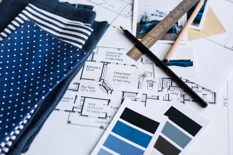 Interior designers working table. Interior designer's working table, an architectural plan of the house, a color palette, furniture and fabric samples in blue royalty free stock photos