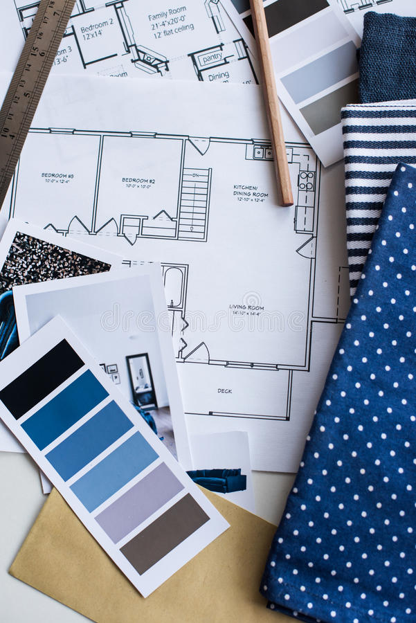 Interior designers working table. Interior designer's working table, an architectural plan of the house, a color palette, furniture and fabric samples in blue stock photography