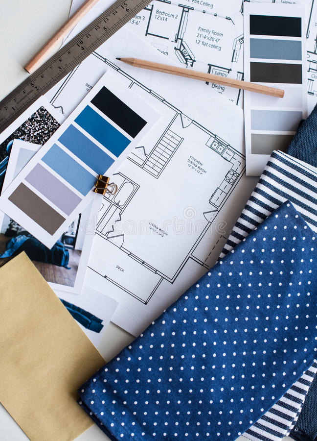 Interior designers working table. Interior designer's working table, an architectural plan of the house, a color palette, furniture and fabric samples in blue stock images