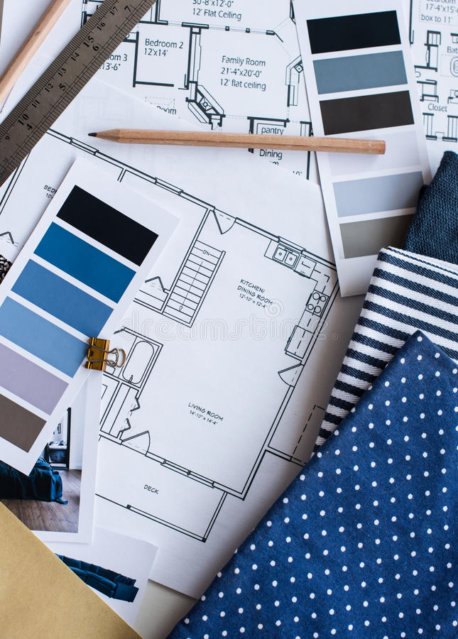 Interior designers working table. Interior designer's working table, an architectural plan of the house, a color palette, furniture and fabric samples in blue stock photo
