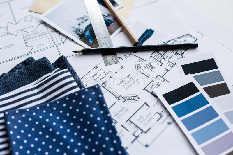 Interior designers working table. Interior designer's working table, an architectural plan of the house, a color palette, furniture and fabric samples in blue royalty free stock images