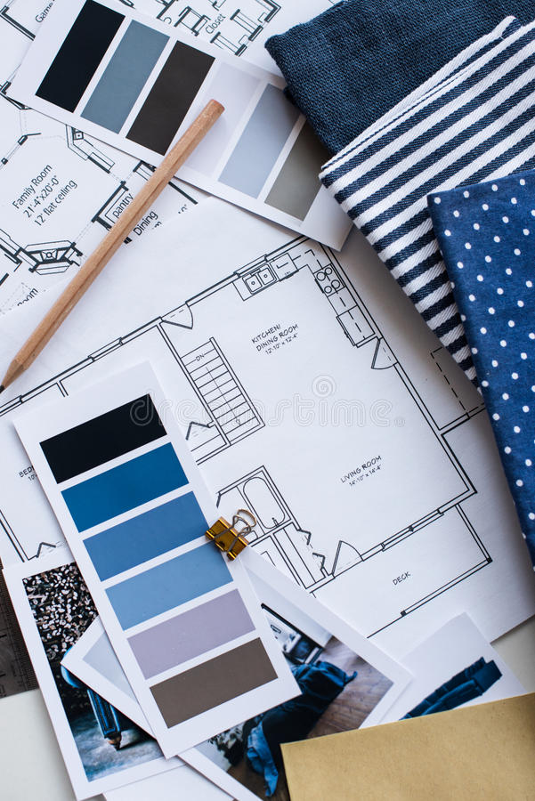 Interior designers working table. Interior designer's working table, an architectural plan of the house, a color palette, furniture and fabric samples in blue royalty free stock photo