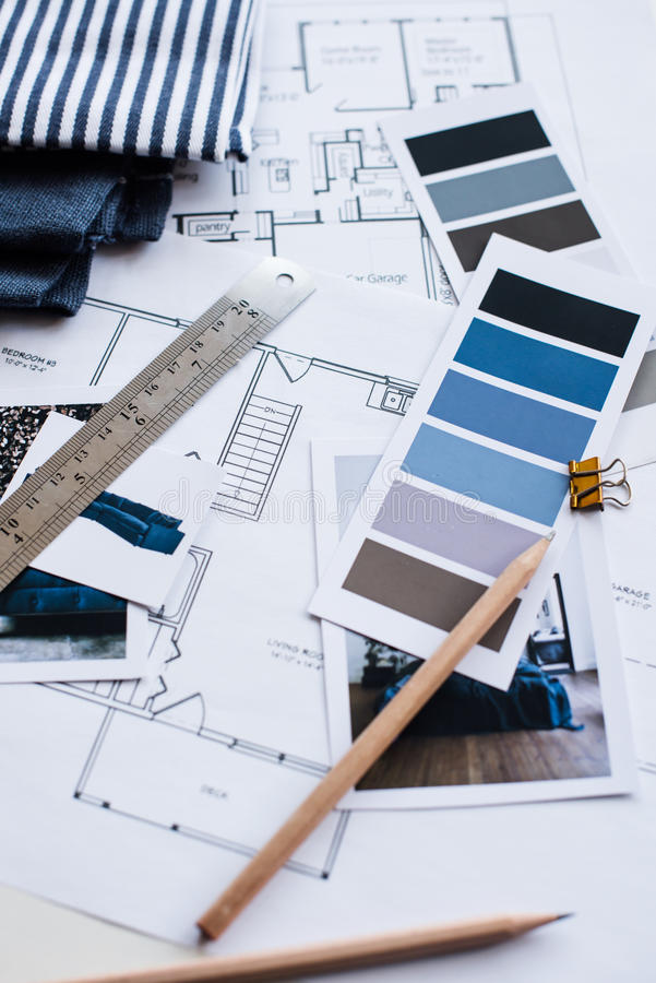 Interior designers working table. Interior designer's working table, an architectural plan of the house, a color palette, furniture and fabric samples in blue royalty free stock image