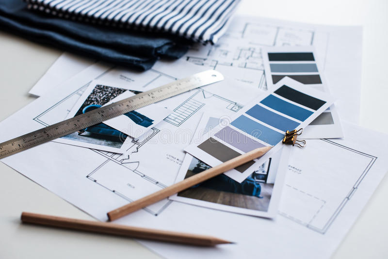 Interior designers working table. Interior designer's working table, an architectural plan of the house, a color palette, furniture and fabric samples in blue stock image