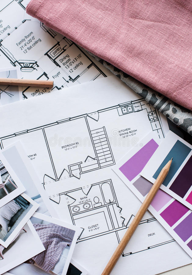 Interior designers working table. Interior designer's working table, an architectural plan of the house, a color palette, furniture and fabric samples in grey stock photography