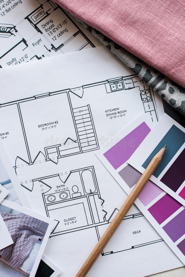 Interior designers working table. Interior designer's working table, an architectural plan of the house, a color palette, furniture and fabric samples in grey royalty free stock photos