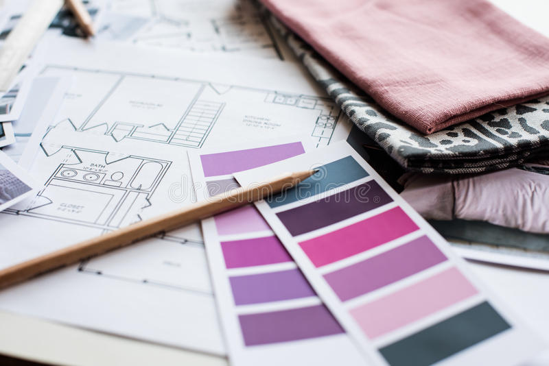 Interior designers working table. Interior designer's working table, an architectural plan of the house, a color palette, furniture and fabric samples in grey royalty free stock photo