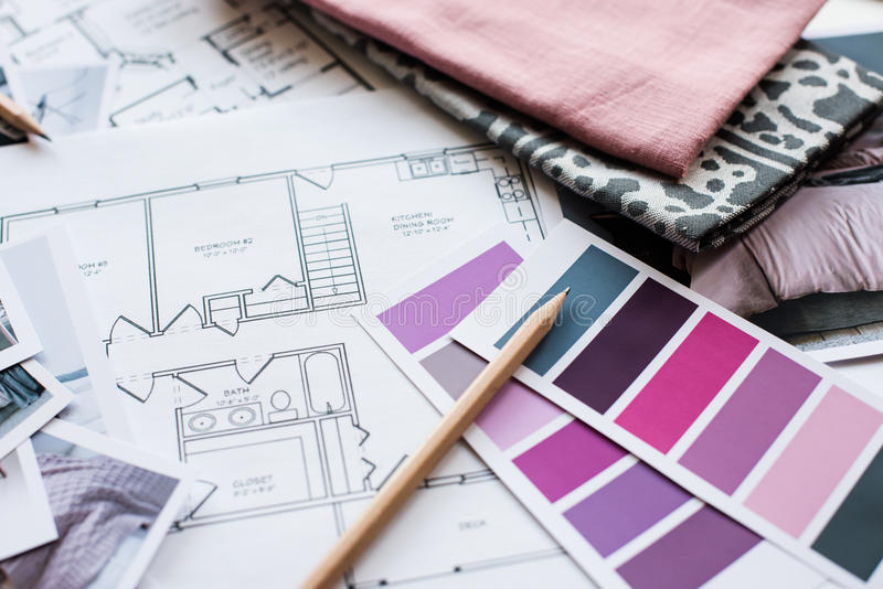 Interior designers working table. Interior designer's working table, an architectural plan of the house, a color palette, furniture and fabric samples in grey stock photo