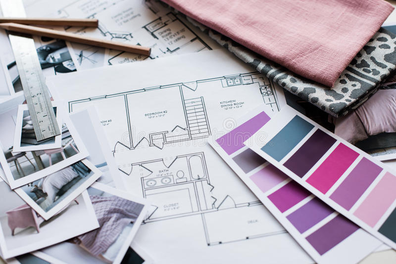 Interior designers working table. Interior designer's working table, an architectural plan of the house, a color palette, furniture and fabric samples in grey royalty free stock images