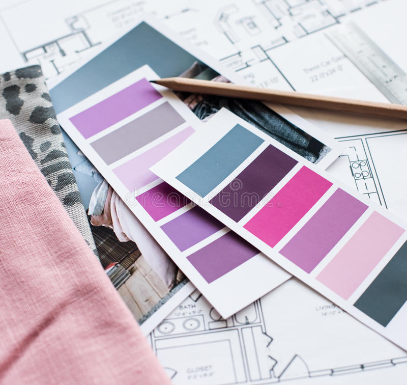 Interior designers working table. Interior designer's working table, an architectural plan of the house, a color palette, furniture and fabric samples in grey royalty free stock photography