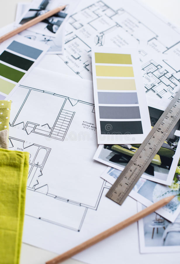 Interior designers working table. Interior designer's working table, an architectural plan of the house, a color palette, furniture and fabric samples in yellow stock photography