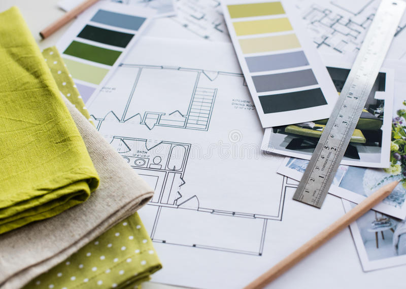Interior designers working table. Interior designer's working table, an architectural plan of the house, a color palette, furniture and fabric samples in yellow royalty free stock photo