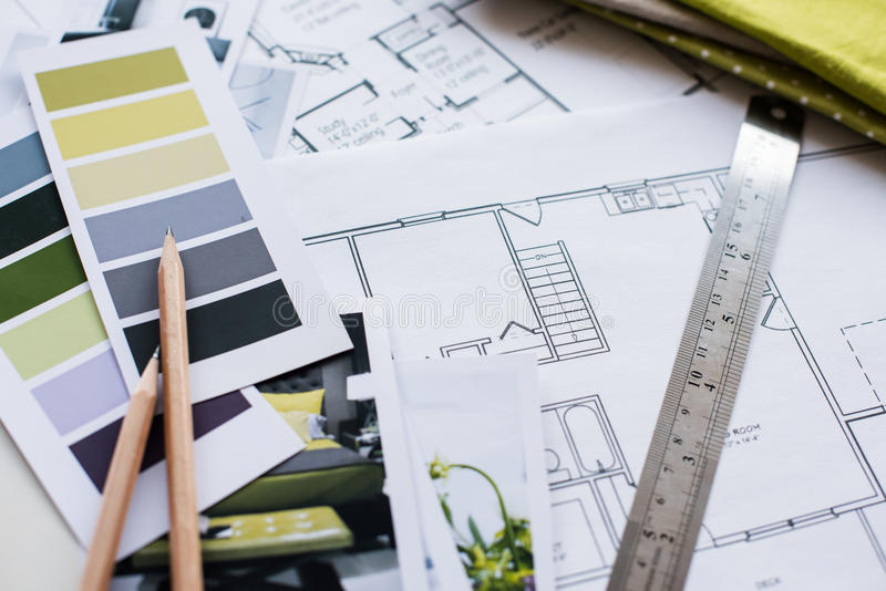 Interior designers working table. Interior designer's working table, an architectural plan of the house, a color palette, furniture and fabric samples in yellow stock image