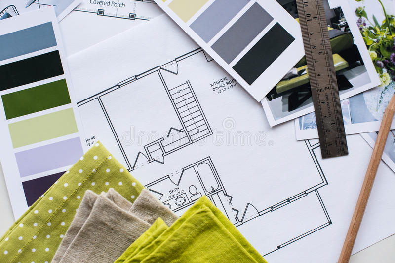 Interior designers working table. Interior designer's working table, an architectural plan of the house, a color palette, furniture and fabric samples in yellow stock photo