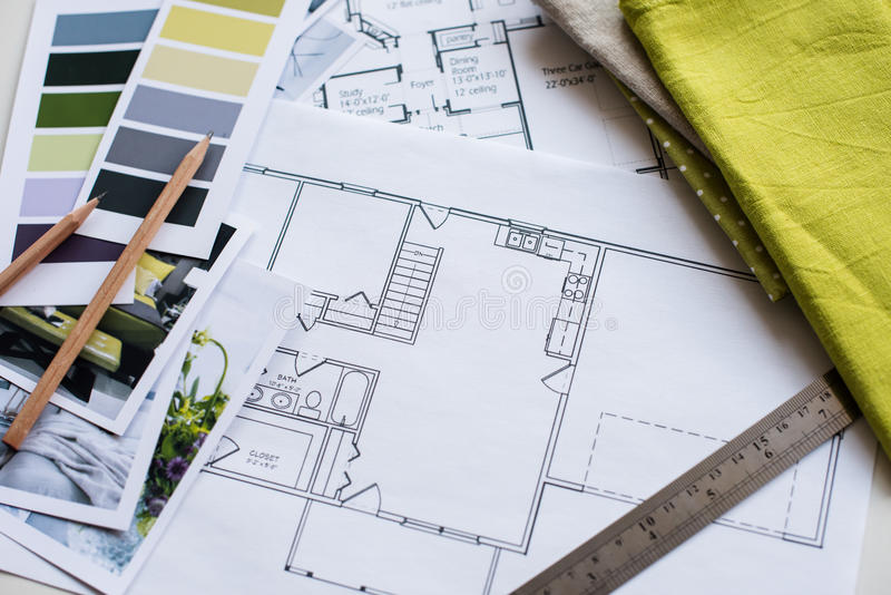 Interior designers working table. Interior designer's working table, an architectural plan of the house, a color palette, furniture and fabric samples in yellow stock images