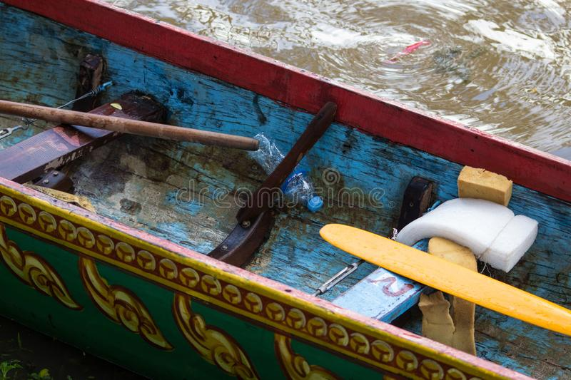 Interior detail of wooden racing boat after a traditional racing event in Cambodia, revealing paddles, painted detail, and water b. Medium close up interior of stock photography