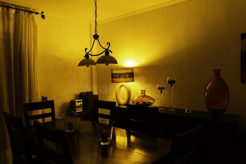 Interior of dining room with vintage lamp, glass vase and candlesticks on chest of drawers, wooden table and chairs in night-time stock image