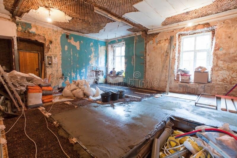 Interior do apartamento com materiais durante na renovação e a construção que fazem a parede da placa de gesso da gipsita foto de stock royalty free